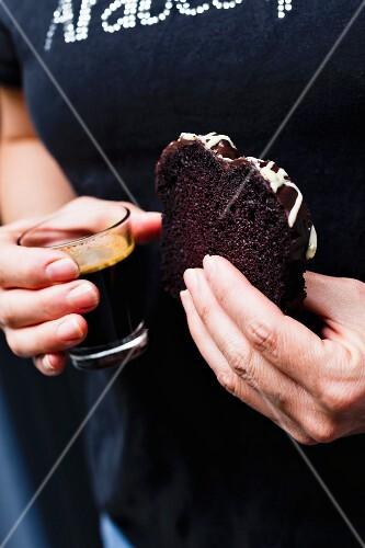 A woman holding a glass of coffee and a slice of chocolate sponge cake with chocolate glaze