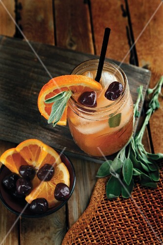 Apple and bourbon cocktail with oranges and cherries