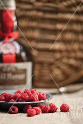 Fresh raspberries with a bottle of liqueur in the background
