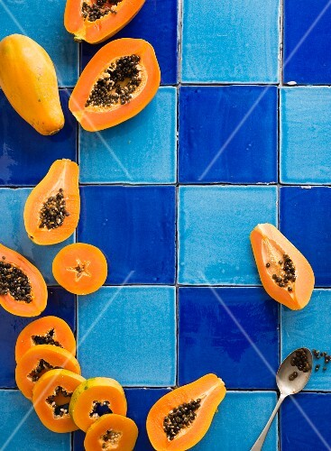 Fresh papayas, whole and sliced, on a blue tiled surface