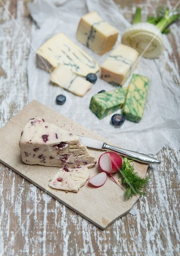 Wensleydale, Jacobean sage, Cambozola, Morbier with fennel, radishes and blueberries on a wooden board and a piece of paper