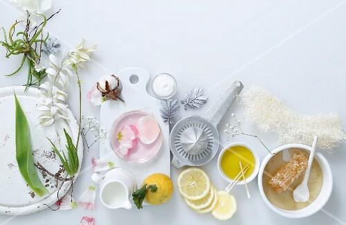 An arrangement of flowers, lemons, oil and honey