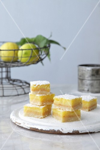 Lemon slices with a wire basket of lemons in the background