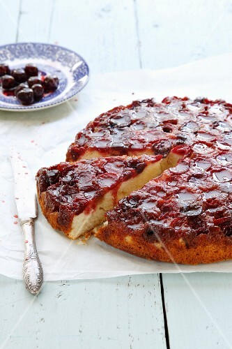 Cherry cake, sliced, on a piece of baking paper