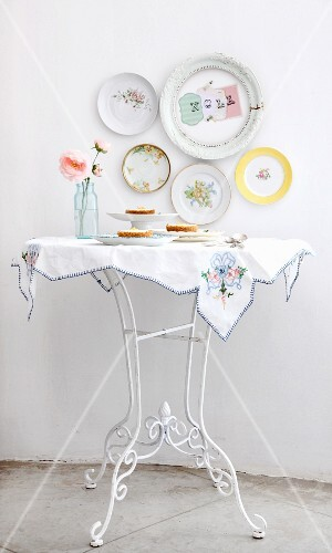 Cheesecakes on white table below decorative plates on the wall