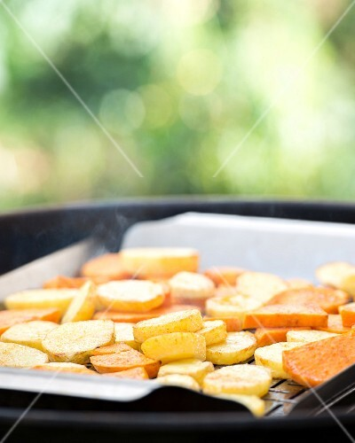 Sliced potatoes on a barbecue