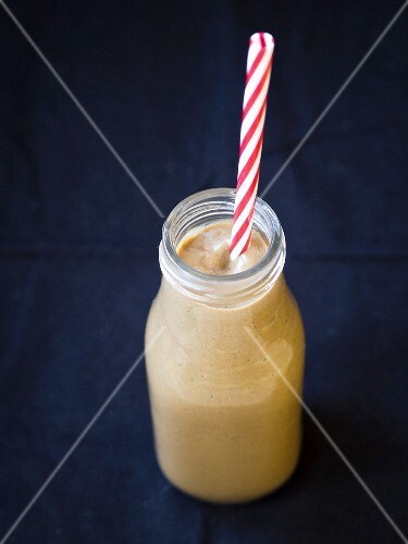 A vegan avocado and chocolate smoothie in a bottle with a straw