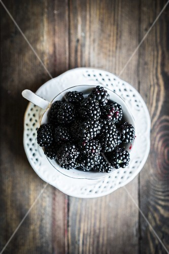 Fresh blackberries in a teacup on a wooden table