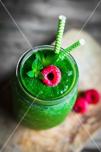 A green smoothie garnished with a raspberry