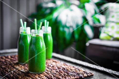 Fresh green smoothie in glass bottles with straws