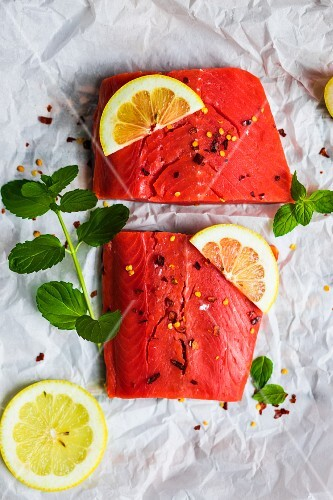 Raw wild salmon with mint, lemon and spices on a piece of white paper