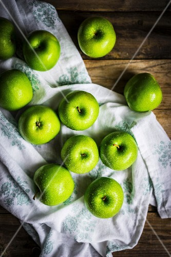 Bright green apples on wooden surface