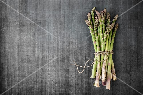 A bundle of asparagus on a grey surface