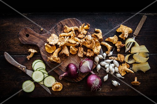 An arrangement of chanterelle mushrooms, red onions, pearl onions and cucumber slices