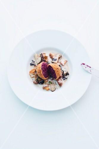 A red cabbage dumpling on a mushroom ragout