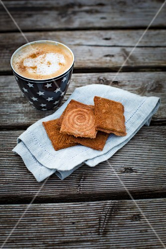 Cinnamon waffles with a cappuccino on a piece of greaseproof paper