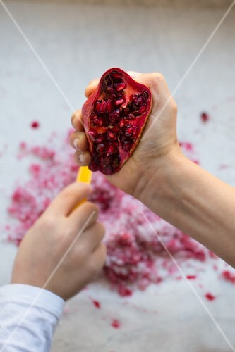 A child's hand squashing a pomegranate