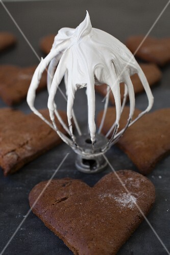 Gingerbread hearts and a whisk with an icing sugar-egg white glaze