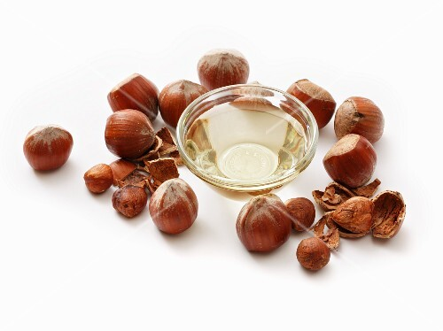A bowl of hazelnut oil surrounded by hazelnuts