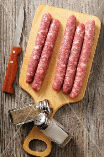 Chipolata sausages on a wooden board with a knife, pepper and salt