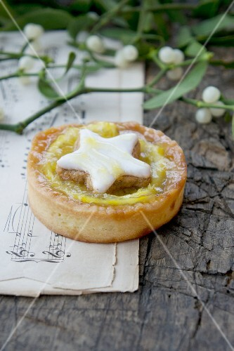 An orange tartlet decorated with a cinnamon star with mistletoe sprigs on a piece of sheet music