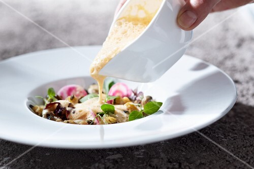 Salad being drizzled with a dressing