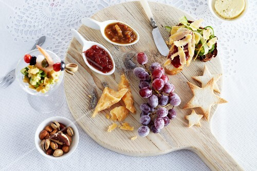 A Christmas cheese platter with grapes and various sauces