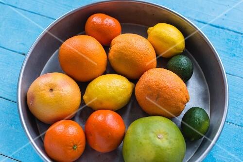 Various citrus fruits in a metal bowl