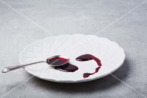 Pomegranate syrup on a plate with a spoon