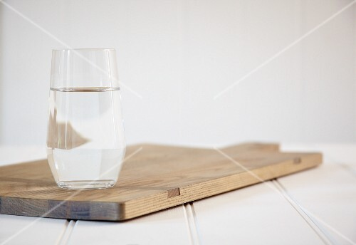 A glass of water on a chopping board
