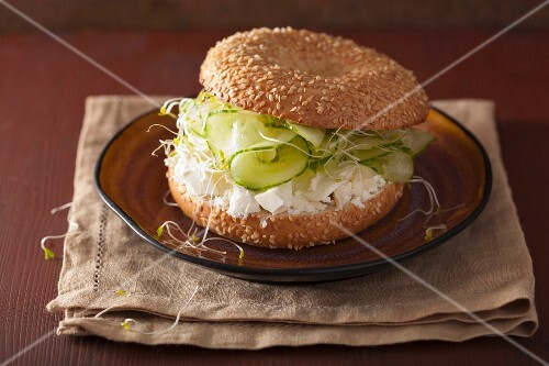 A bagel filled with cucumber, feta cheese and alfalfa sprouts