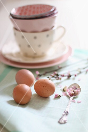 Eggs and flowers in front of stacked teacups