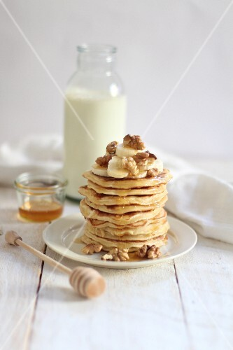 A stack of pancakes with bananas and nuts