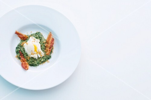 A poached egg on a bed of creamy spinach with crispy bacon