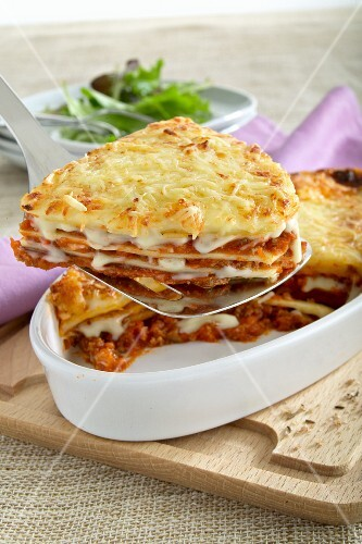 A slice of lasagne being removed from the baking dish