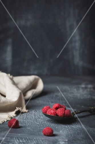 Fresh raspberries on a spoon on dark surface