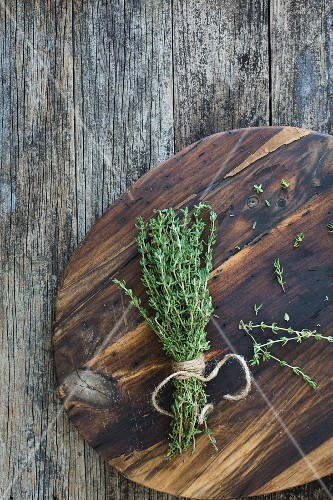 A bundle of fresh thyme on a wooden plate