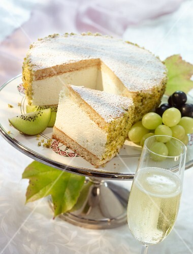 A creamy cheesecake garnished with kiwis and grapes