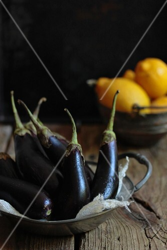 Baby aubergines and lemons on a wooden surface