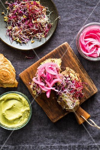 Sandwiches with avocado cream, beansprouts and pickled red onions