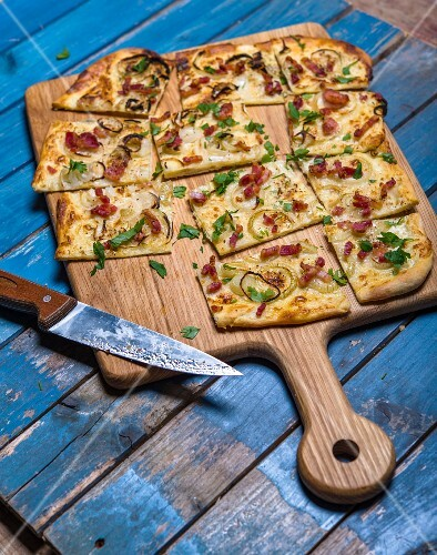 Tarte flambée with bacon and onions on a chopping board