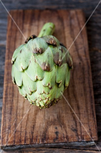An artichoke on a wooden board