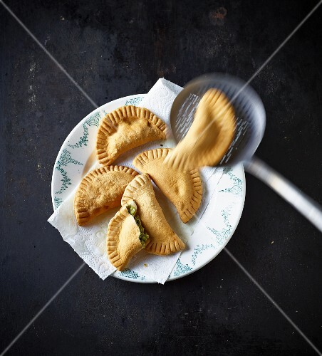 Tirteln (deep-fried pastries from South Tyrol) on a plate and a draining spoon