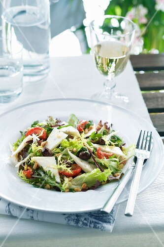 A mixed green salad with pine nuts, olives and fenugreek cheese
