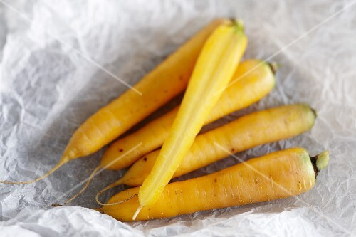Yellow carrots on a piece of white parchment paper