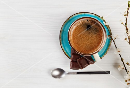 A cup of coffee with pieces of chocolate (seen from above)