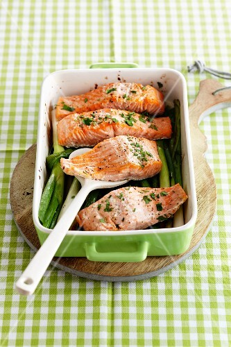 Roasted salmon fillets on spring onions