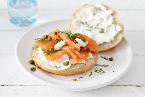 A bread roll topped with smoked salmon, goat's cream cheese and capers