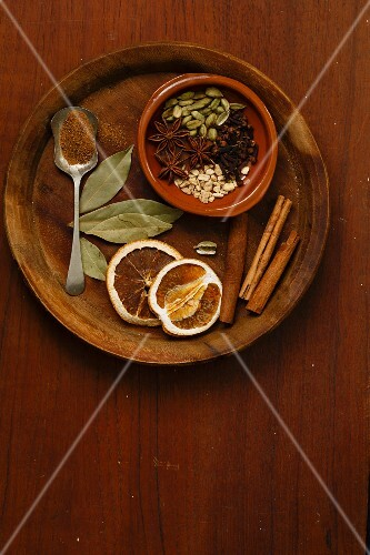 Various spices for mulled wine on a wooden plate