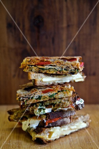 A stack of various grilled sandwiches to take away